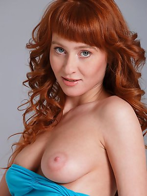 Redhead Oxavia strips and flaunts her sexy body and unshaven pussy on the bed.
